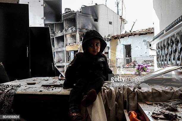 TOPSHOT A child sits in front of the wreckage of a blast damaged building on January 14 2016 in Diyarbakir Six people died and 39 others were wounded...