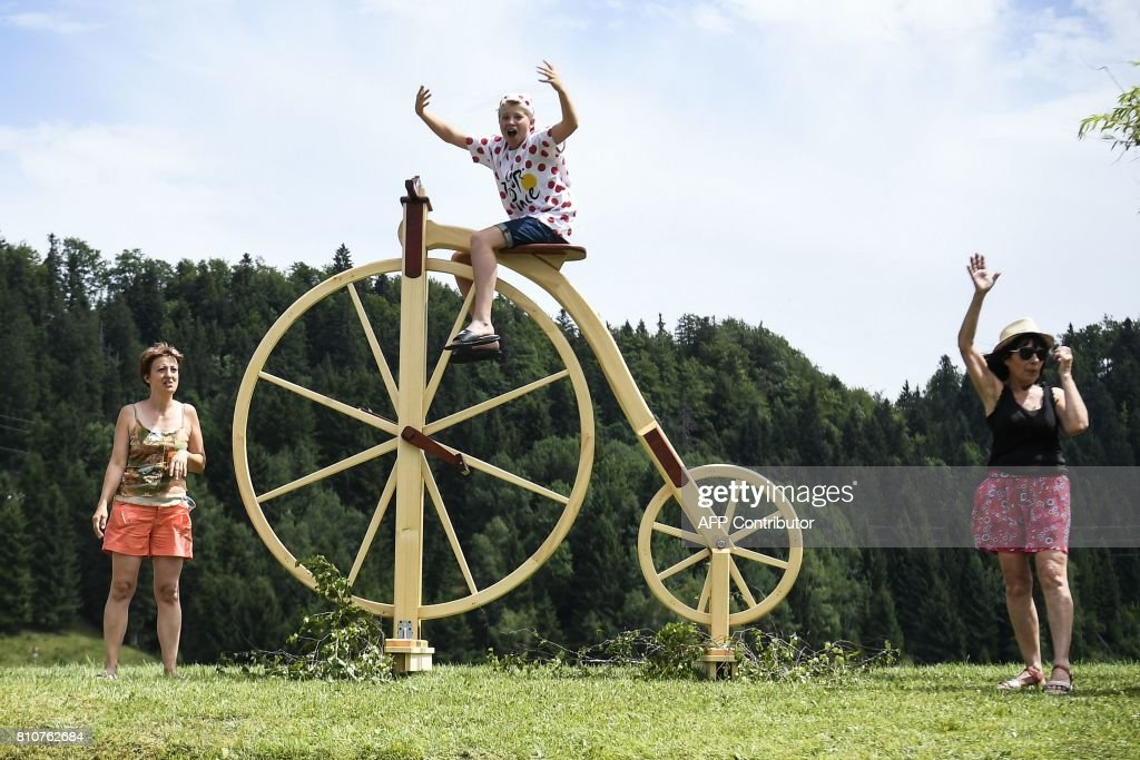 A child sits on a giant wooden sculpture shaped as a penny-farthing as supporters cheer along the road during the 187,5 km eighth stage of the 104th edition of the Tour de France cycling race on July 8, 2017 between Dole and Station des Rousses. / AFP PHOTO / Lionel BONAVENTURE