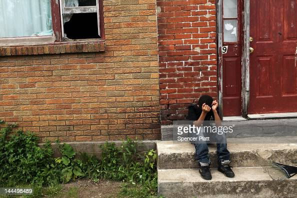 A child sits on a stoop in a working class section of Utica on May 14 2012 in Utica New York Like many upstate New York communities Utica is...