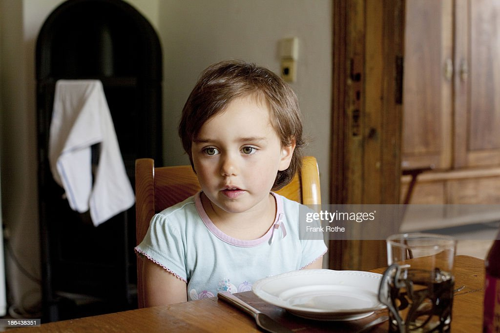 child sits on a table and looks nice and relaxed : Stock Photo