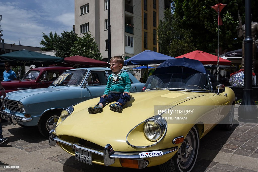 A child sits on a vintage car displayed during the 11th Old Timers Fest on May 29, 2016 in Prizren. / AFP / ARMEND