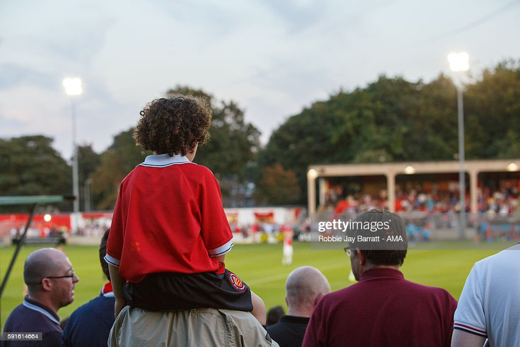 A child sits on the shoulders to watch the Salford City v FC United of Manchester match at Moor Lane stadium home of Salford City during the Vanarama...