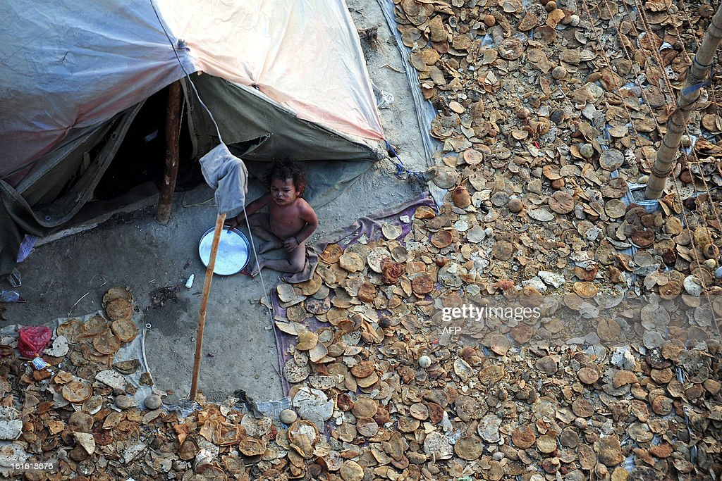 A child sits outside the tent of sanitation workers amid pieces of chapati (flatbread), collected from the food scraps of other devotees and dried in the sun for later consumption, during the Maha Kumbh Mela in Allahabad on February 13, 2013. The Kumbh Mela in the town of Allahabad will see up to 100 million worshippers gather over 55 days to take a ritual bath in the holy waters, believed to cleanse sins and bestow blessings.