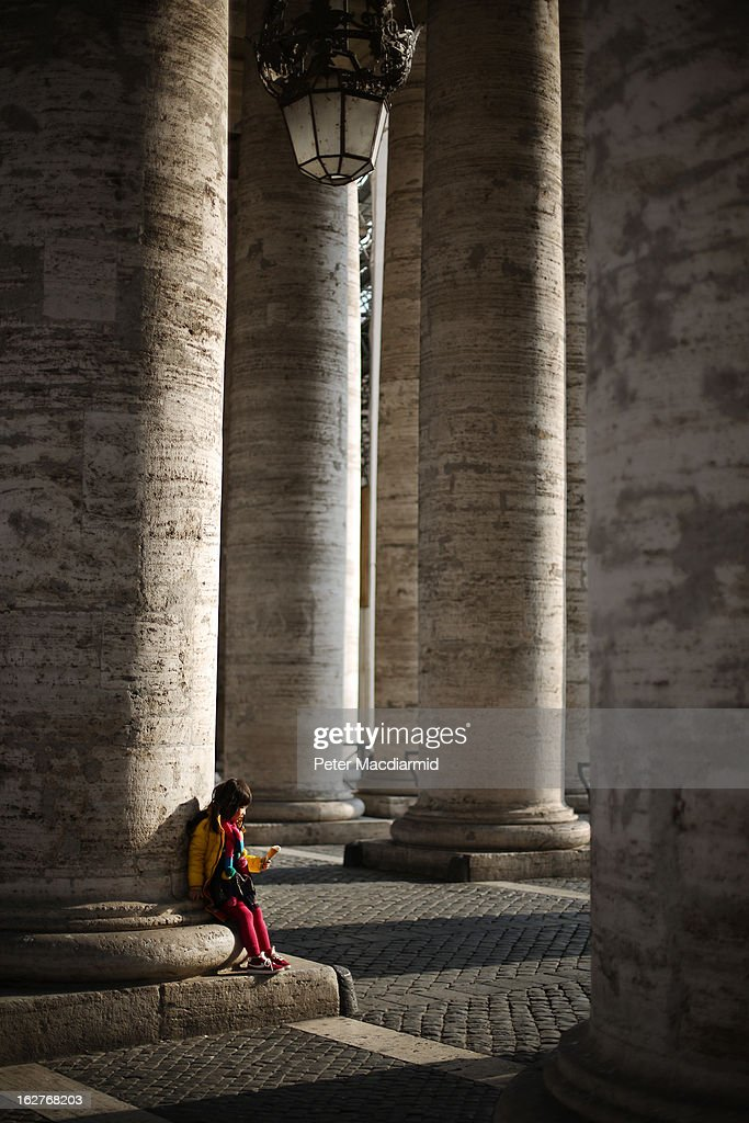A child sits under The Colonnade on February 26, 2013 in Vatican City, Vatican. The Pontiff will hold his last weekly public audience on February 27, 2013 before he retires the following day. Pope Benedict XVI has been the leader of the Catholic Church for eight years and is the first Pope to retire since 1415. He cites ailing health as his reason for retirement and will spend the rest of his life in solitude away from public engagements