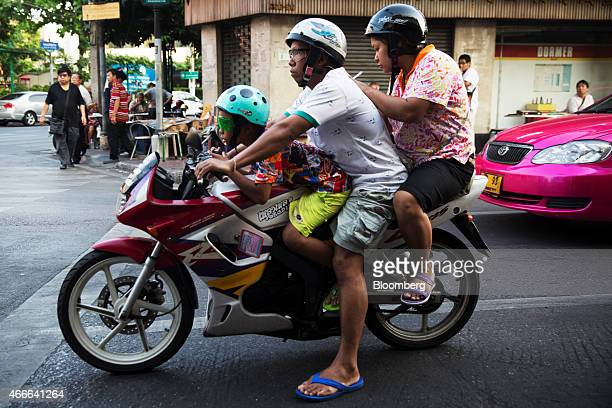A child sits with adults on a motorcycle in the Chinatown area of Bangkok Thailand on Sunday March 15 2015 Almost a third of Thailand's population...
