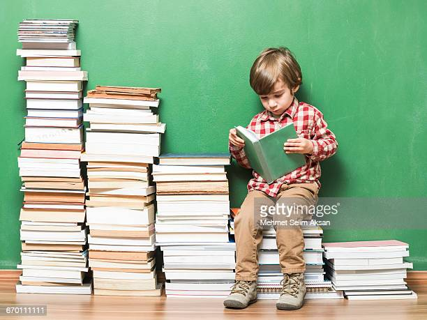 Child Sitting And Reading On Ladder Made Of Books