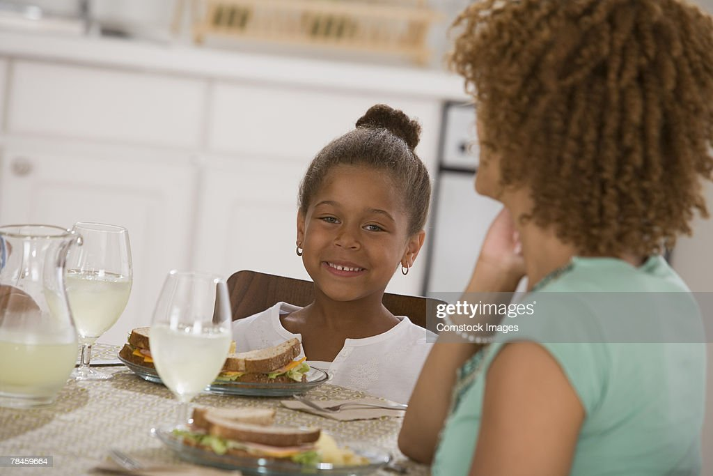Child sitting at table with woman : Stock Photo