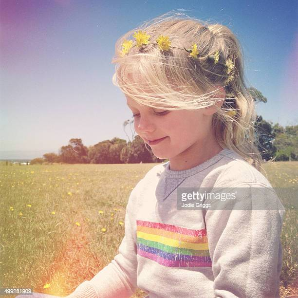 Child sitting in sun with daisy chain around head