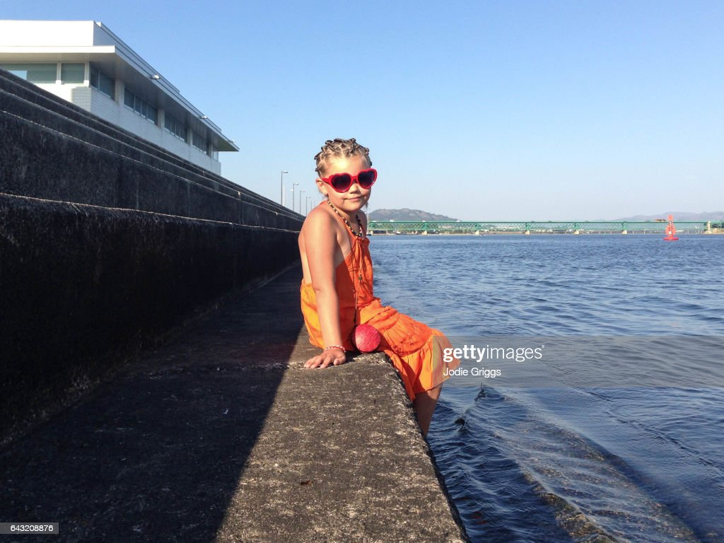 Happy child wearing heart shaped glasses sitting on a concrete step on the edge of a river dipping feet into the water