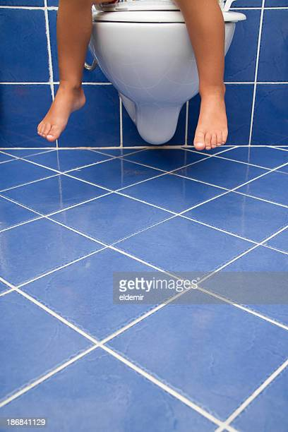Child sitting on a toilet in a blue tiled bathroom
