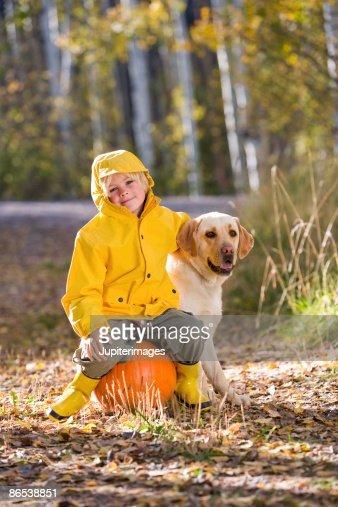 Child sitting on pumpkin with dog : Stock Photo