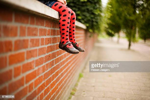 Child sitting on red brick wall in dotted tights