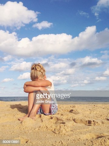 Child Sitting On Sand At The Beach With Head Down Stock