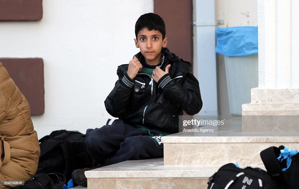 A child sitting on stairs as Refugees wait outside the Fethiye District Police Department Directorate after Turkey 122 refugees were captured in the Aegean Sea on February 9, 2016. Total of 122 refugees were captured by Turkish coast guards while they were illegally trying to reach Greece's Rhodes island through the Aegean Sea.
