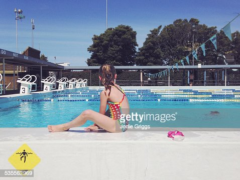Child sitting on the edge of swimming pool