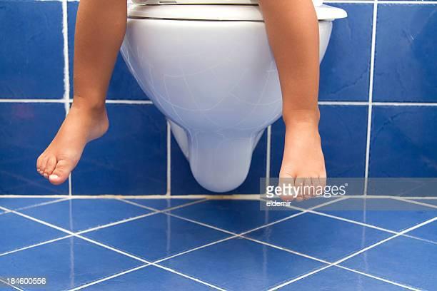 Kind sitzt auf der Toilette