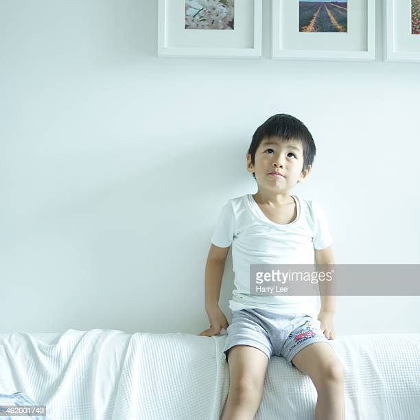 Child sitting on top of sofa looking up