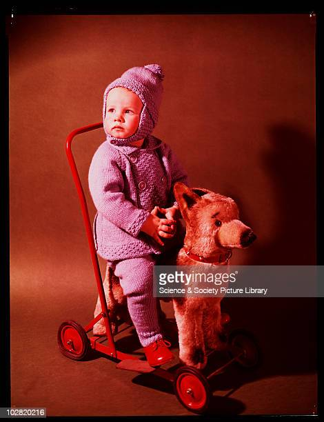 Child sitting on toy dog c1950 Photographic Advertising Limited founded in 1926 created multipurpose stock images with the potential for selling a...