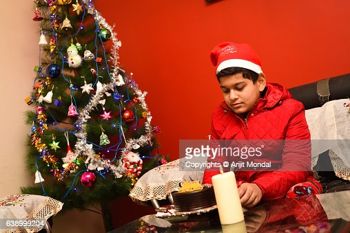Child Sitting with Christmas Cake, Christmas Tree and Candle