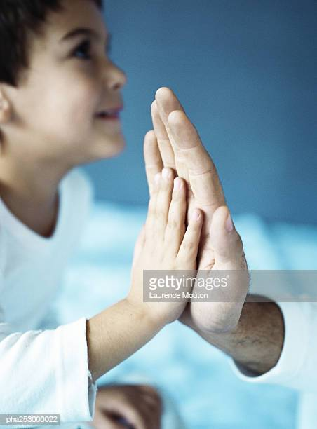 Child slapping adult's hand in a high five, close-up