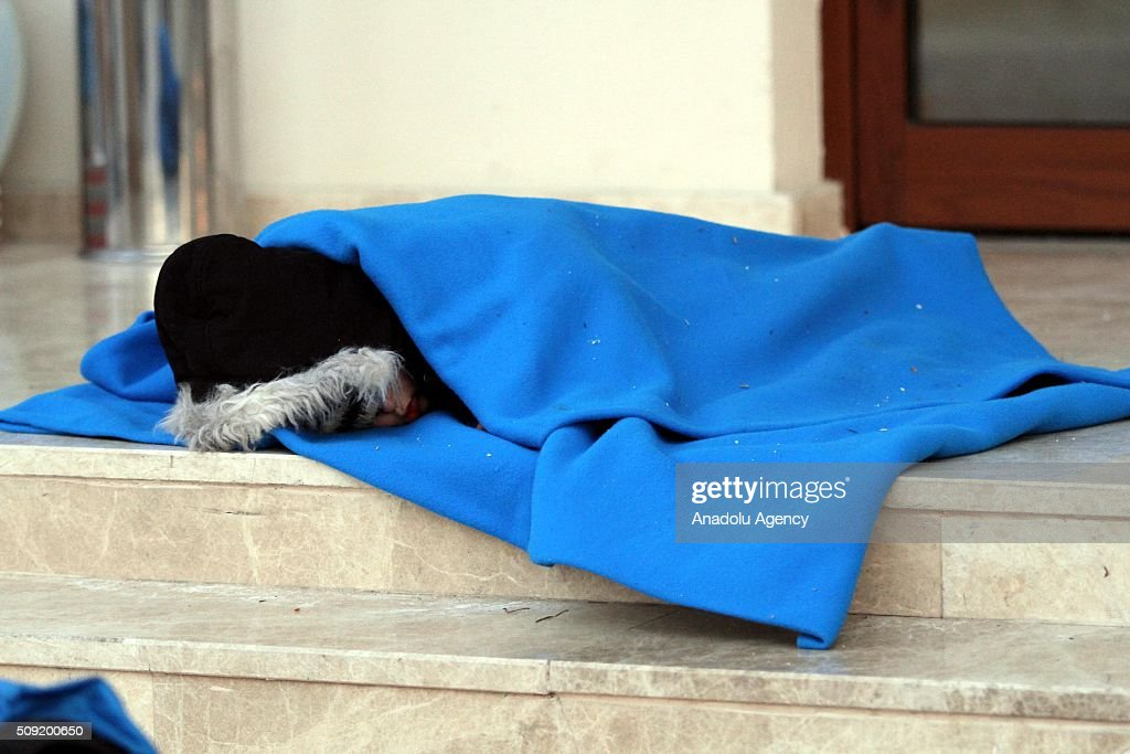 A child sleeping on stairs as Refugees wait outside the Fethiye District Police Department Directorate after Turkey 122 refugees were captured in the Aegean Sea on February 9, 2016. Total of 122 refugees were captured by Turkish coast guards while they were illegally trying to reach Greece's Rhodes island through the Aegean Sea.
