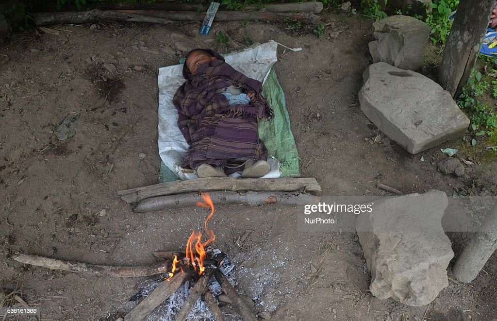 A child sleeps on a temporary hut with fire to keep warm as parent work at water bedded rice paddy field for plantation at Shajouba Village in the Senapati district of India north eastern state of Manipur on Tuesday, May 31, 2016. Over 70 percent of Indians depend on farm incomes and about 65 percent of the country's farms depend on monsoon rains that fall between June and September. Photo by Caisii Mao