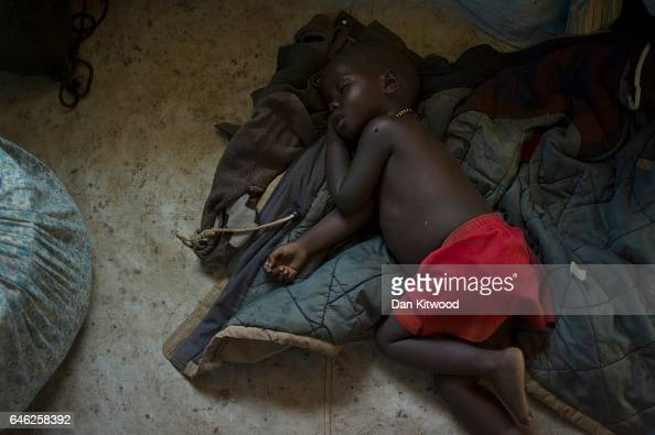 A child sleeps on the floor of a tent at the Kuluba Collection Point after being brought from the South Sudanese border on February 24 2017 in Kuluba...