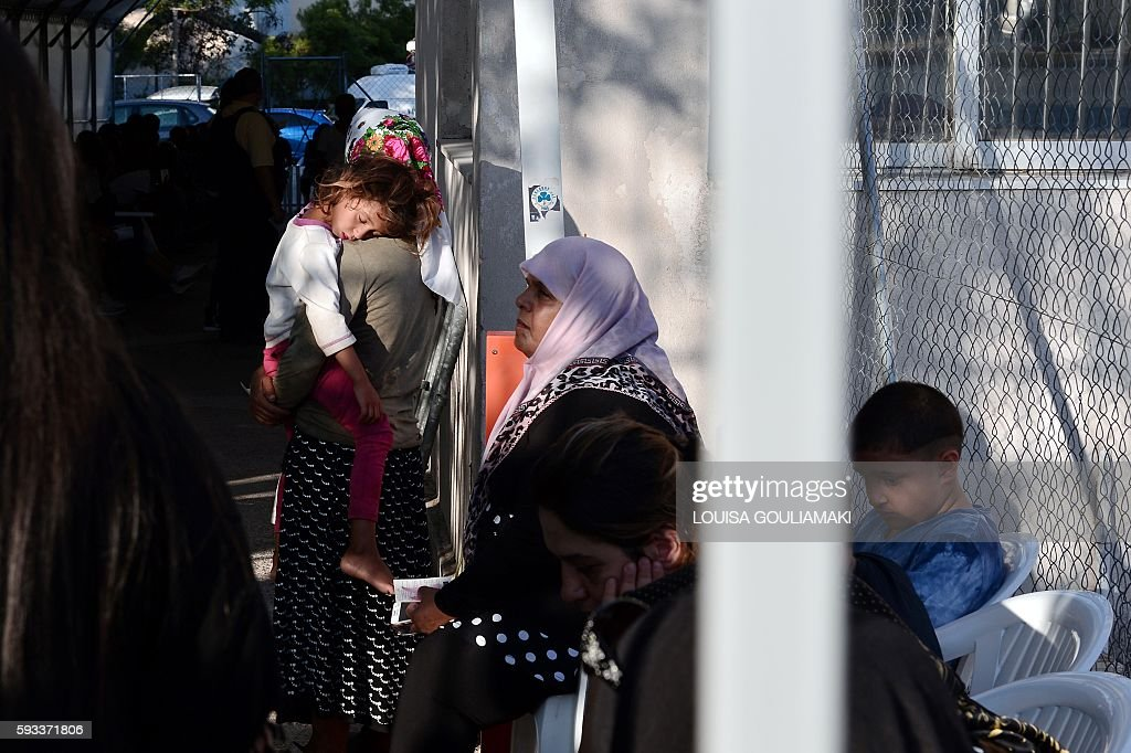 A child sleeps on the shoulder of a woman as sheand other refugees and migrants wait at the offices of an asylum service in Athens for their hearing...
