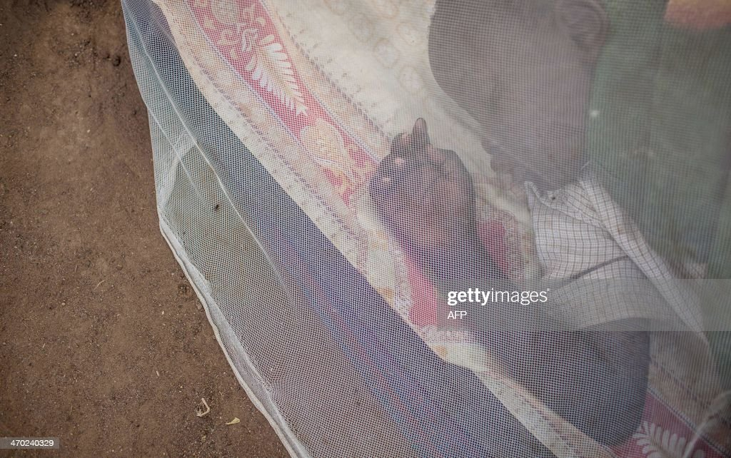 A child sleeps under a mosquito net in the Tongping UNMISS (United Nations Mission in South Sudan) base, where over 27,000 people seeked refuge, on February 19, 2014, in Juba. Increasing ethnic violence seeded in Juba has spread across the country like a cancer, annexing whole communities now being categorised and mobilised by clan, and has trumped any notion of national unity less than three years after South Sudan won independence from Khartoum. AFP PHOTO / ANDREI PUNGOVSCHI