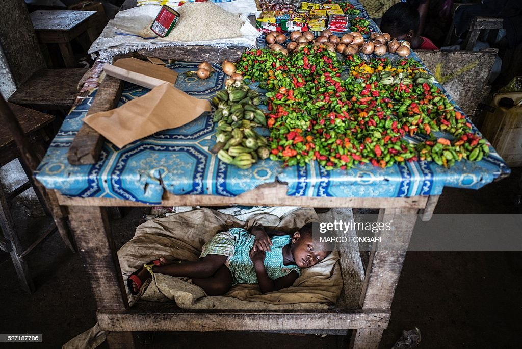 A child sleeps under a table at the Jorkpan market in Sinkor district in Monrovia, on May 2, 2016. / AFP / MARCO