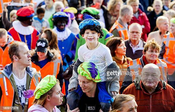 A child smiles as a few hundred people some of them dressed up as Zwarte Piet take part in a demonstration in favor of the character SaintNicholas'...