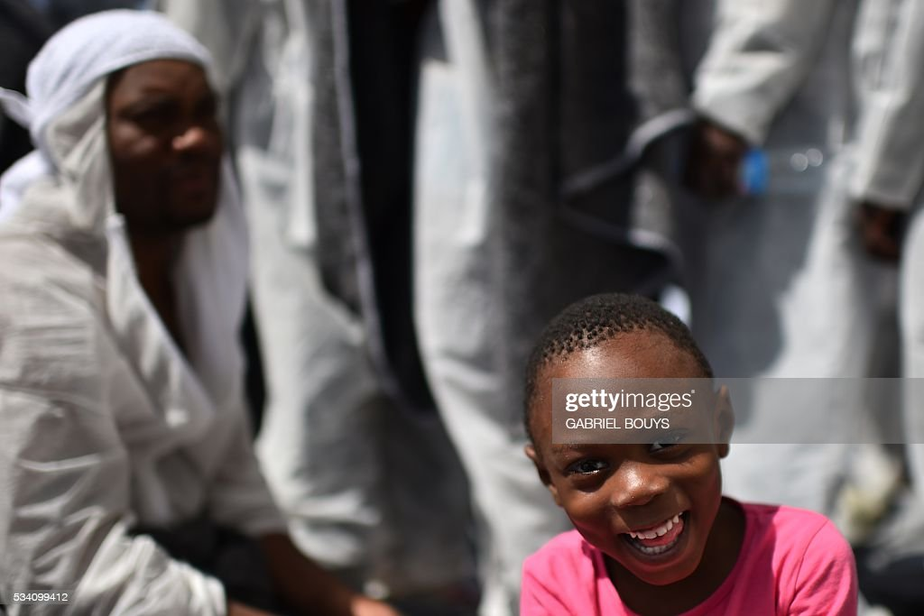 A child smiles during a distribution of meals aboard the rescue ship 'Aquarius', on May 25, 2016 a day after a rescue operation of migrants and refugees off the Libyan coast. The Aquarius is a former North Atlantic fisheries protection ship now used by humanitarians SOS Mediterranee and Medecins Sans Frontieres (Doctors without Borders) which patrols to rescue migrants and refugees trying to reach Europe crossing the Mediterranean sea aboard rubber boats or old fishing boat. / AFP / GABRIEL
