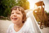 Child smiling after slide at park