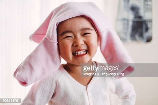 Child smiling cheerfully at camera on bed