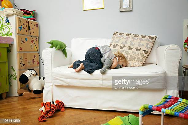 child, sofa, holding, toy, face down