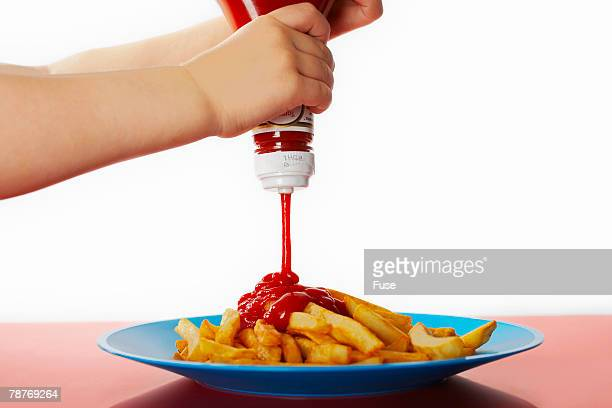 Child Squeezing Ketchup on French Fries