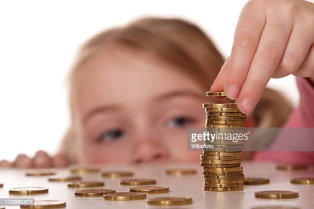 A child stacking coins on a table