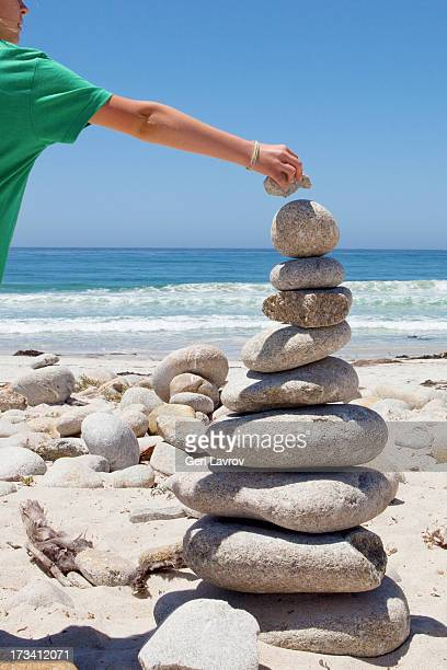 Child stacking rocks at the beach