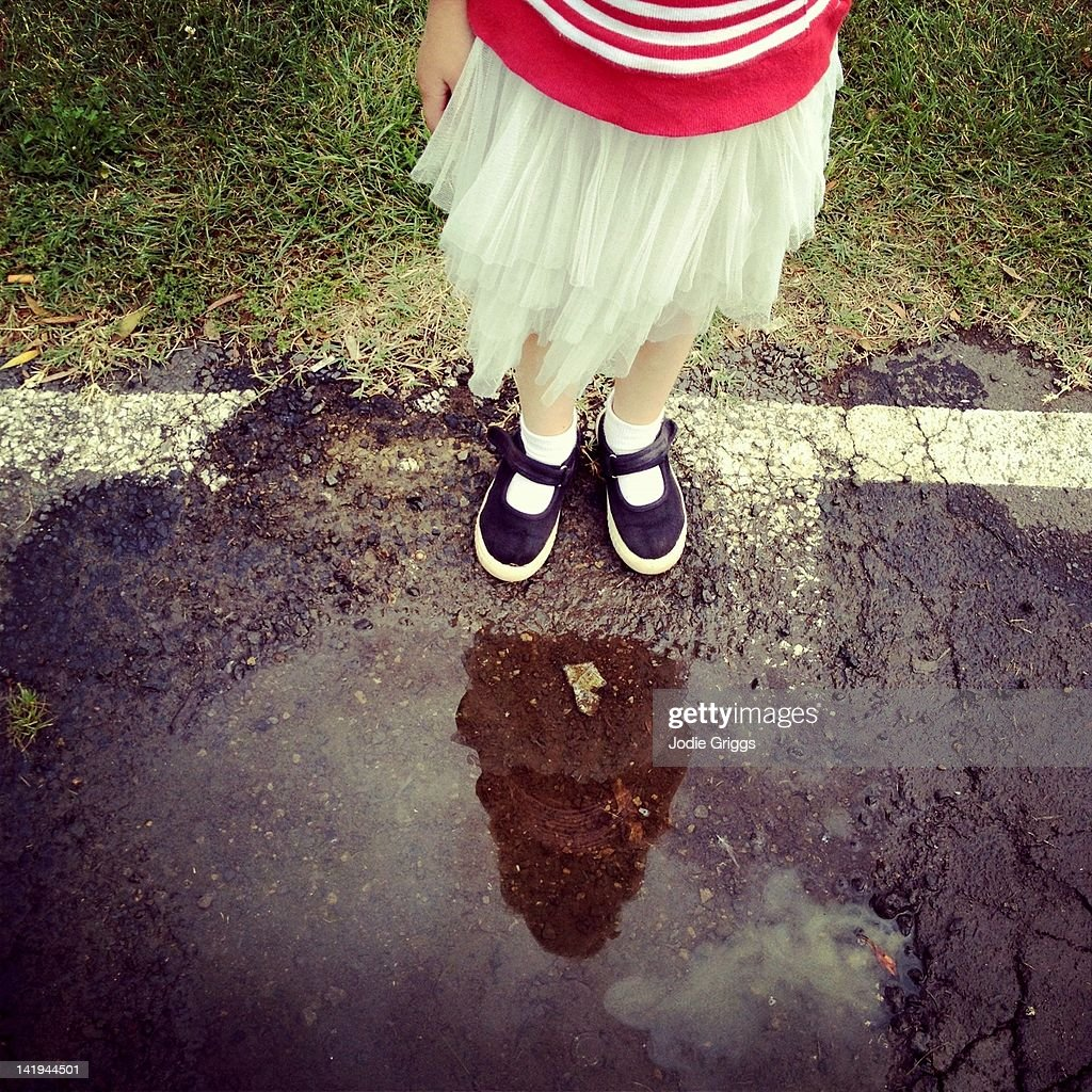 Child standing at edge of puddle : Stock Photo