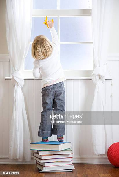 child standing on a stack of books looking out the window