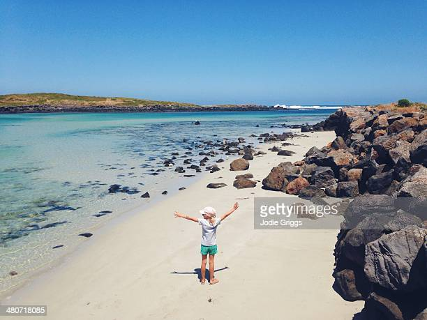 Child standing on beach with arms outstretched