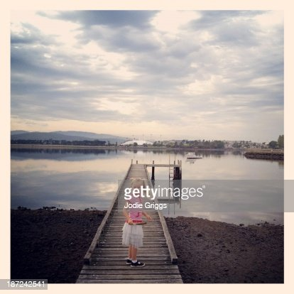 Child standing on wooden jetty by the river : Stock Photo