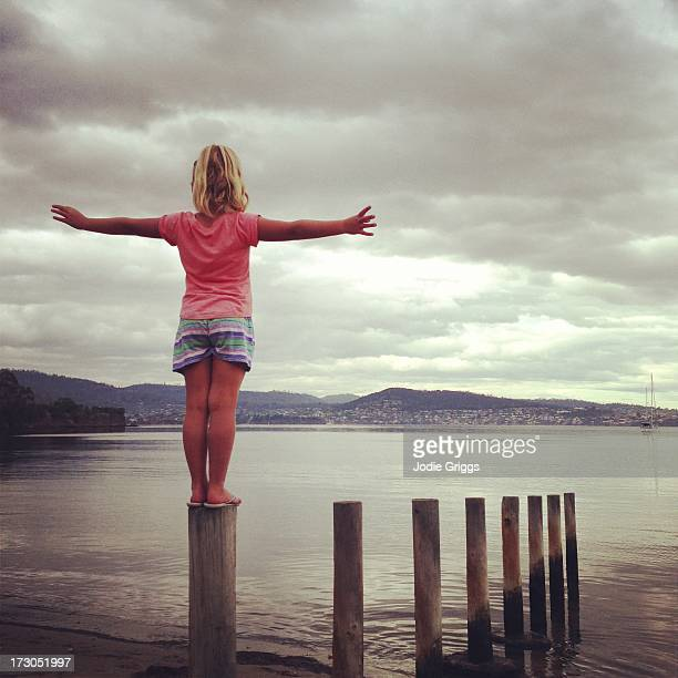 Child standing on wooden post looking out at river