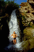 Child Standing Under Waterfall