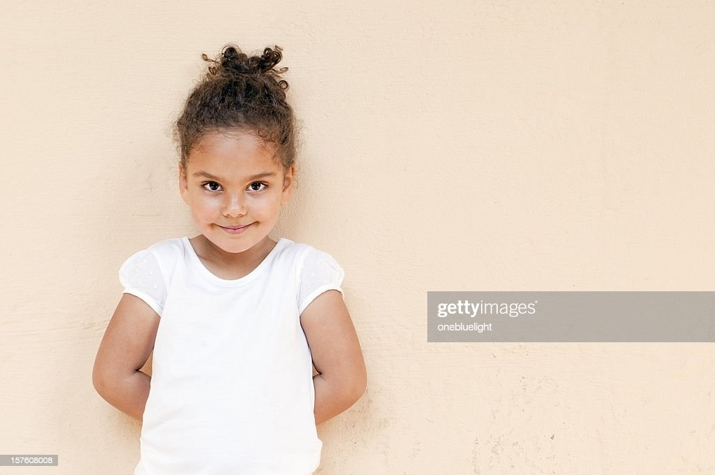 Child Standing Up Against Wall With Hands Behind Her Back ...