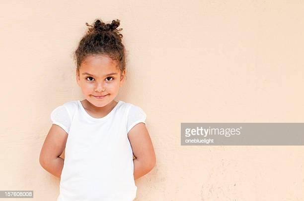 Bambino in piedi contro la parete con le mani dietro la schiena