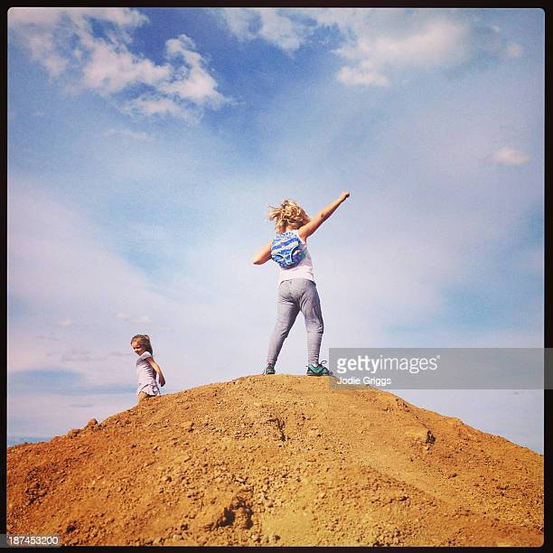 Child standing victoriously on large dirt pile