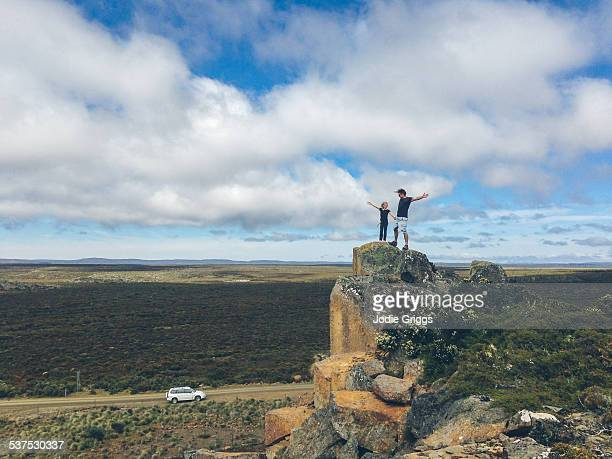 Child standing with father on high rocky outcrop