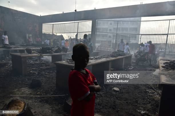 A child stands amid debris in the market after a fire devastated the building during the night on September 18 2017 in Abobo neighborhood of Abidjan...