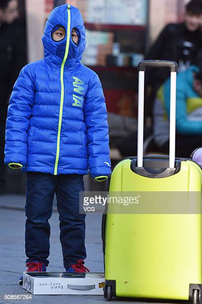 A child stands as he heads back home with families for the upcoming Spring Festival at Beijing West Railway Station on February 5 2016 in Beijing...